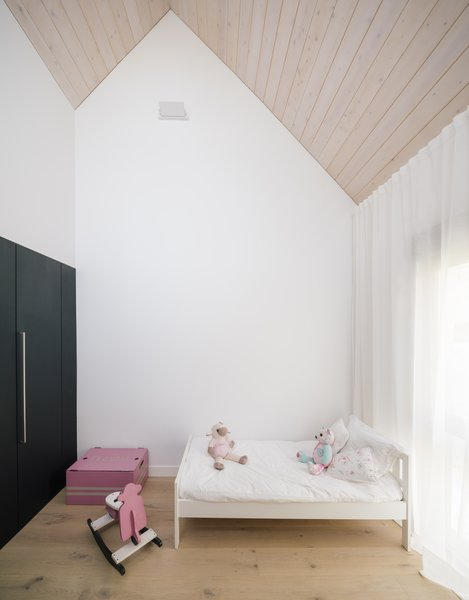 Upstairs, the gables of the sawtooth roof house individual bedrooms: two for children, and a larger master suite.