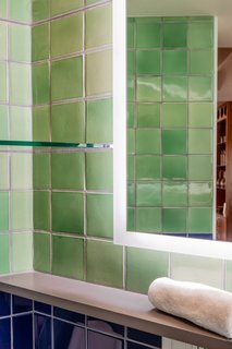 The handmade tiles provide just the right amount of light reflection while giving the bathroom a handcrafted touch.