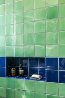A shower niche houses toiletries for guests, who sometimes stay for several weeks at a time.
