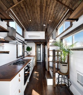 The interior reveals a well-lit, warm, and cozy space that is largely dominated by the full-size kitchen, although there is still space for a full bath in the back and a full-sized sofa that can open into to a guest bed.