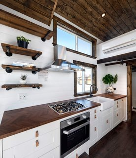 The kitchen has a propane cooktop and oven, ventilated by a stainless steel hood above. A clerestory window and another strategically located in front of the sink keep the kitchen well lit.