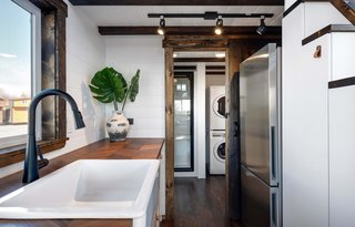 The kitchen's refrigerator and cabinets are efficiently tucked under the steps up to the sleeping loft.