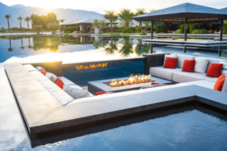 This poolside conversation pit is oriented around a fire pit at a vacation home in Coachella, California.