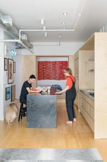 The open, 920-square-foot loft felt right to homeowners and creative couple Aubrey Ament and Will Glaser, but they needed to separate public and private spaces. A thick wall of storage did the trick.