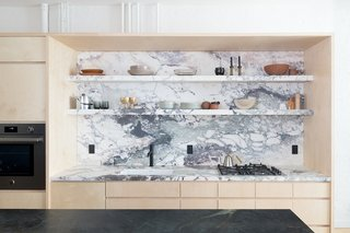 Breccia Capraia marble continues from the countertop to form the backsplash and open shelving.