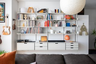 A shelving system in the living room displays books, decor, and the couple's vinyl collection.