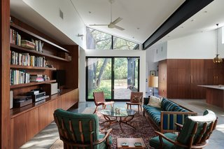 The interiors feature a combination of midcentury furniture, modern materials and detailing, older pieces from the homeowner's collection, and splashes of color and pattern.