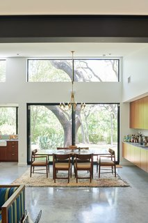 Wood cabinetry links the dining area to the kitchen, and the sliding glass doors provide a view to the oak trees on the site.