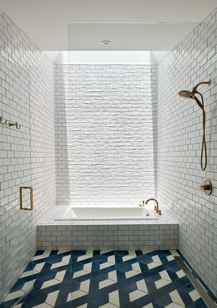 A central bathroom features a tiled bathtub under a skylight. The walls are covered in a glossy white tile, and the floors with a geometric blue and white matte tile.