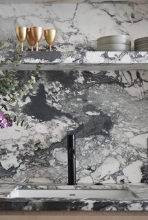 Dean selected a black faucet and a white sink bowl rather than a more typical metallic finish so that both would blend better with the active veining of the black and white marble.