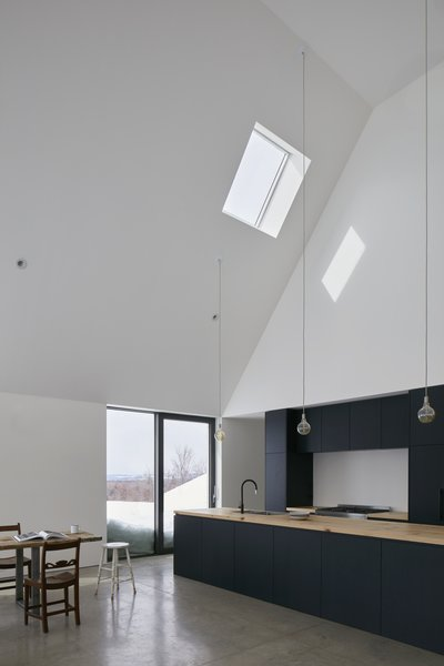 The kitchen has matte-black cabinetry and a black faucet at the sink that create an understated, streamlined composition. A skylight provides additional light in the double-height space.