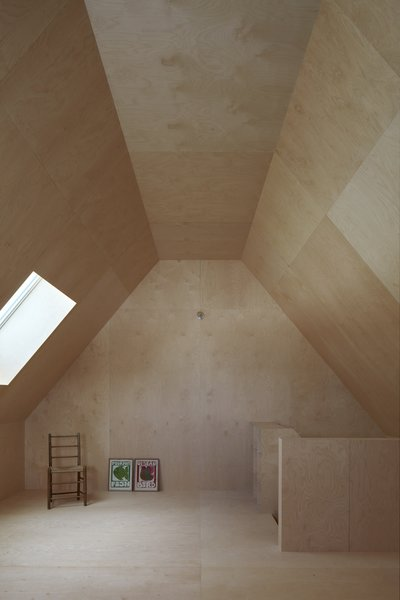 The gable roofs of the house are expressed on the second floor, where the lofted ceilings are covered with birch plywood.