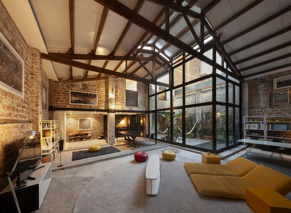 The L-shaped central space has high ceilings and holds the dining room, living room, kitchen, and work area.