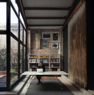 The original wood doors from the front facade were relocated to the interior, where they function as sliding doors.