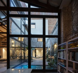 An outdoor patio was created simply by removing a portion of the roof of the building. It acts more as an extension of the interior than as a back or side yard.