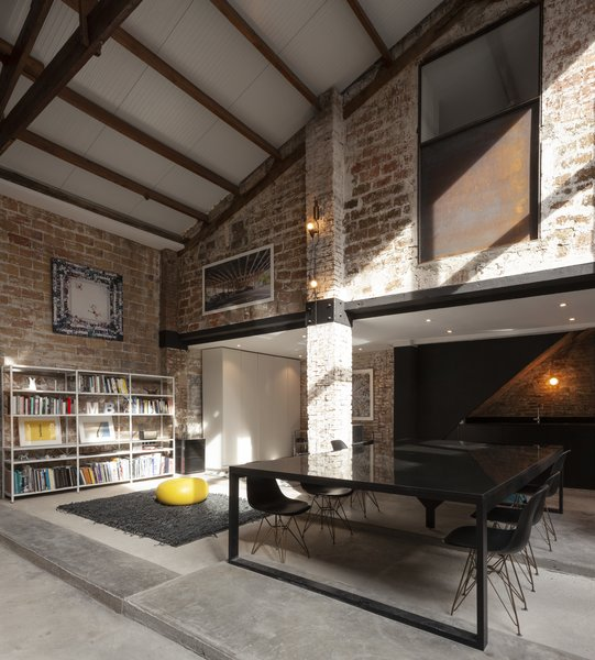 Modern steel structural elements contrast with the existing wood roof beams and trusses and brick columns and walls.