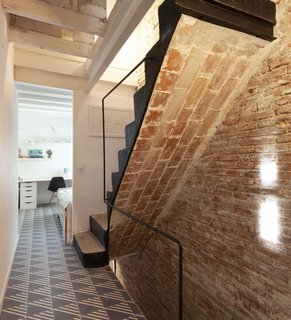 The bedrooms at the rear of the building, located in the former fly loft, are accessed off of an existing masonry staircase. The floors are covered in new cement tiles.