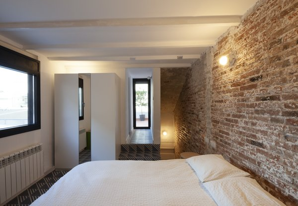The bedrooms receive light from windows that have been punched out of the masonry and overlook the outdoor patio below.