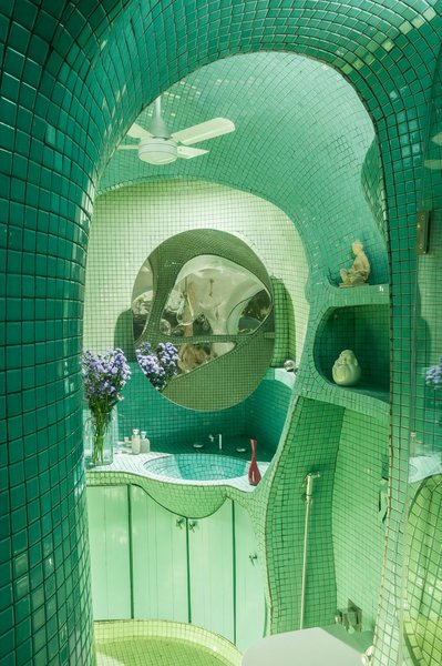 In the bathroom, the teal mosaic tile hug the curves of the walls, ceiling, and built-in shelving.