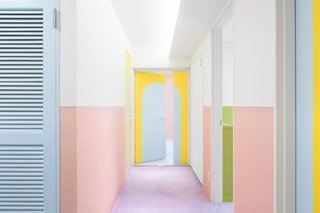 Walls in the corridor are lined with pink wainscotting, while the white upper portion provides a moment of visual relief and balance. A vibrant yellow at the end of the corridor draws the eye down the hallway.