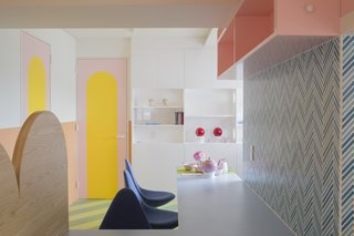 Painted arches in contrasting colors are found throughout the apartment; the arched motif is repeated in wood in the kitchen.