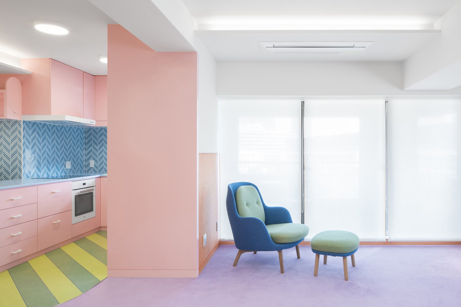 The rosy, dull pink of the kitchen cabinets bleeds into the living room but is starkly contrasted with the striped green-and-yellow floor and blue backsplash in the kitchen and furniture in the living room.