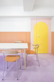 The pastel tangerine chairs in the dining area pick up the orange wainscotting of the walls, and the simple lines of the dining furniture allow the walls and finishes to function as artwork.