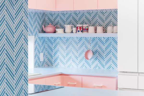 The light blue tiles of the kitchen vary in color and are arranged in a graphically arresting herringbone pattern that offers a pleasant respite from the cotton-candy pink of the cabinetry.