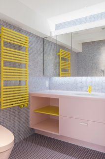Even in the bathrooms, there are moments of bright color: a yellow faucet, a pink and yellow vanity, a yellow towel heater. The mosaic tile on the floor is of a different color than that of the walls, but together they create a pleasing backdrop for the bolder tones in the small room.