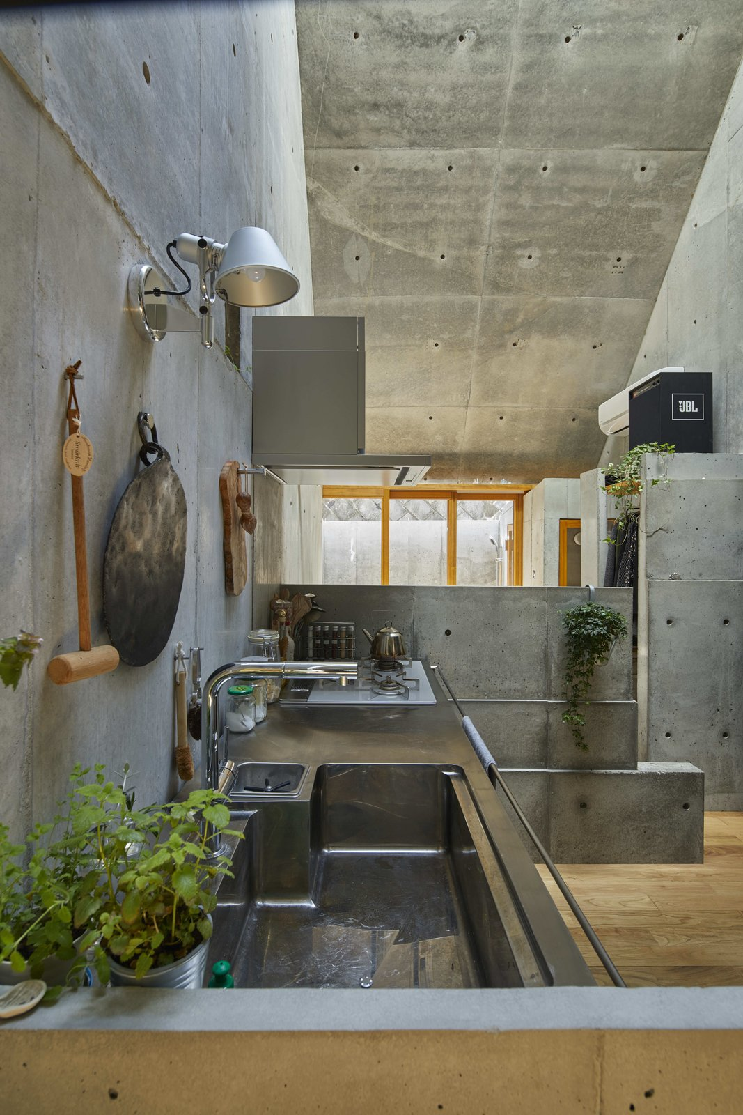 Kitchen, Medium Hardwood, Concrete, Wall, Range, Undermount, and Concrete The interior maintains a sense of texture from the concrete that isn't overwhelming because of the wood floors and high ceilings.  Best Kitchen Range Medium Hardwood Concrete Concrete Photos from A Concrete Tiny House in Tokyo Opens to the Sky—and the Street