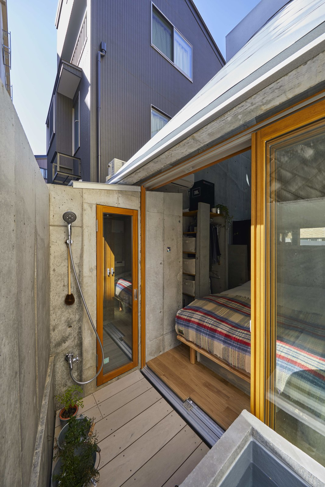 Outdoor, Raised Planters, Back Yard, Hardscapes, Small, and Shower The bedroom opens out onto a small rear deck with potted plants and an outdoor shower.  Outdoor Shower Photos from A Concrete Tiny House in Tokyo Opens to the Sky—and the Street