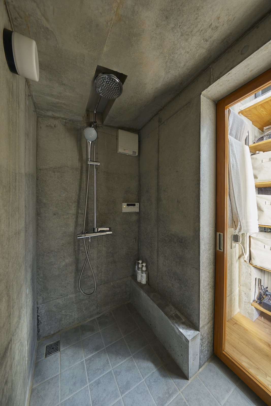 Bath Room, Open Shower, Ceramic Tile Floor, and Wall Lighting The concrete walls of the rest of the home continue into the shower room, where tile floors provide a different scale but similar color palette.  Photo 10 of 12 in A Concrete Tiny House in Tokyo Opens to the Sky—and the Street