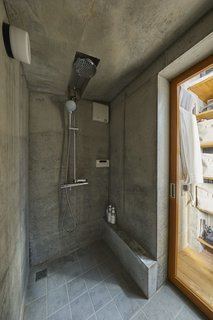 The concrete walls continue into the shower room, where tile floors provide a different scale but a similar color palette.
