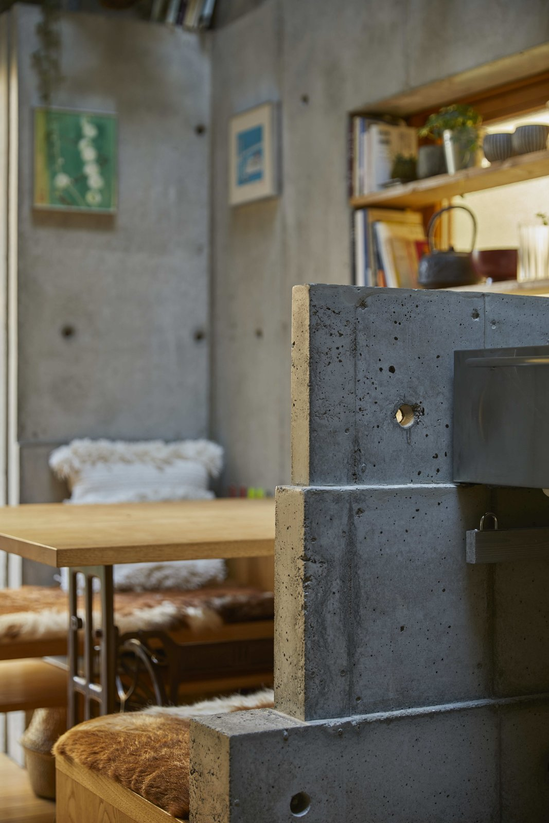 Dining Room, Table, Bench, and Medium Hardwood Floor Sculptural, blocky elements form half-walls and shelving components, allowing the structure of the home to provide multiple uses.  Photo 11 of 12 in A Concrete Tiny House in Tokyo Opens to the Sky—and the Street