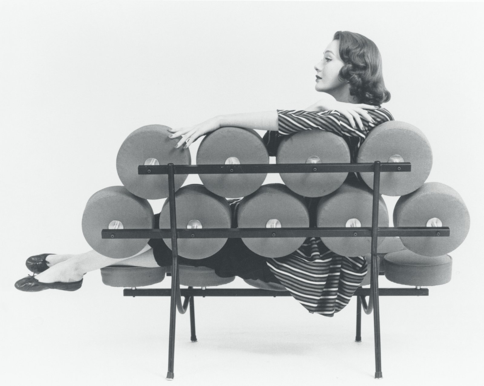 While not the most successful sofa in terms of quantity sold, the Marshmallow Sofa almost immediately became an icon of modern furniture design when it debuted in 1956. The  piece was originally conceived by Irving Harper, a staff designed at George Nelson, who wanted to use new technology that would injection-mold the cushions that essentially formed soft discs attached to a metal frame—a far cry from the chunky, bulky traditional sofas. However, the manufacturing process was unable to produce satisfactory results, and so the team resorted to discs that were plywood-backed and hand-upholstered, resulting in a very expensive—but eye-catching—piece . (The Marshmallow Sofa: promotional photograph featuring George Nelson and Associates receptionist Hilda Longinotti, 1956.)