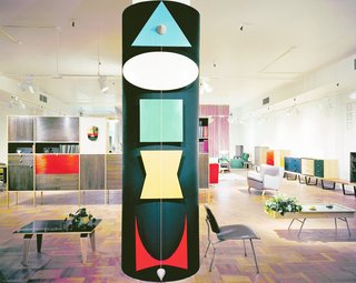 """Yet even before Herman Miller began emphasizing their textiles, the company was working with graphic design and incorporated bold, abstract shapes into their newly refreshed showrooms across the country. The abstract forms see on the column in this Herman Miller showroom in Chicago in 1949 represented the four furniture designers (Isamu Noguchi, George Nelson, Charles Eames, and Paul Laszlo), with the curved, abstract """"M"""" at the bottom emerging as the Herman Miller logo in the 1940s. (Herman Miller Chicago showroom designed by George Nelson & Co., 1949.)"""