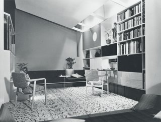 """The regularity of Rohde's pieces for the 1933 Chicago World's fair would be a harbinger of the simple, linear modular designs that would continue to be produced by Herman Miller in the coming years. In 1944, Herman Miller replaced Rohde with designer George Nelson, who developed the Storage Wall and its subsequent iterations. The line was a step in a new direction, with standardized, prefabricated units that caused """"an instant sensation"""" because of their simplicity mixed with unique, functional touches like a light-up mirror at a vanity, phonographs that were hidden away in cabinets that matched other credenzas and items in the same line, and trays that were integrated into coffee tables. These types of details became standard not only for Herman Miller, but for the industry at large, as their collections grew in popularity through the 1940s. In the Basic Storage Components line from 1949, for example, the phonograph was easily hidden away or opened up for use with a pull-down face panel.(George Nelson-designed room display featuring Herman Miller furnishings and Basic Storage Components, 1949.)"""