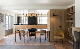 The open kitchen faces a wall of above-counter windows that let in plenty of light. The dining table maintains the material palette of wood and black.