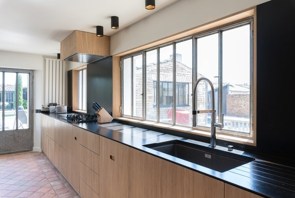 The kitchen is streamlined and modern, with a black seamless backsplash, a minimalist faucet, and a wood-clad vent hood.