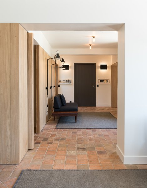 One wall of the entry area and the second living room is entirely clad in solid oak. Here the material forms a minimalist but natural backdrop for a seating area with wall-mounted lighting fixtures.