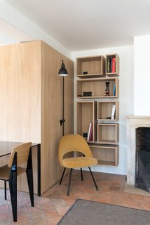 Old meets new at this corner of the living and dining area, where an original mantle with a decorative profile sits comfortably next to open wood shelving with minimalist detailing and a soft yellow chair.