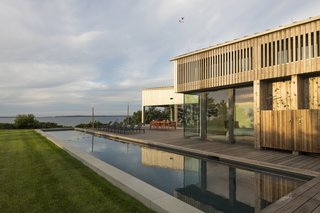 The deck has space for grilling and lounging alongside a lap pool that extends outward to the ocean.