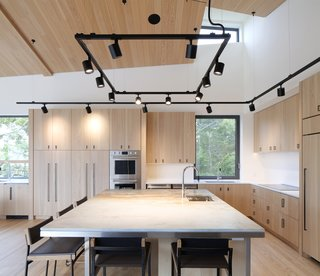 The wood of the kitchen cabinetry is detailed simply, with a minimalist touch and an accent of black, geometric hardware that is picked up in the black track lighting and furniture.