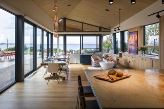 Floor-to-ceiling glazing allows guests to look from the kitchen island into the open living and dining area, and to the ocean views in the distance.