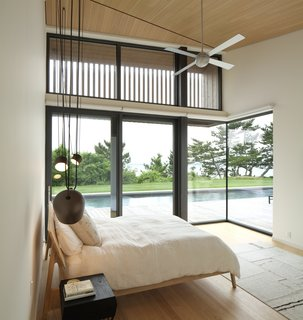 The master bedroom occupies prime real estate in the home, with an entire wall of glass that turns the corner and leads to the lap pool on the deck. Sunlight is filtered at the clerestory level with wood battens and roll-down shades at the lower level.