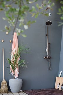 An outdoor shower, tucked away in a more remote part of the open porch, was one of the tricks used to reduce the amount of program for the 100-square-foot interior. Because of the secluded nature of the property and the shielding from shrubs and trees, privacy isn't an issue.