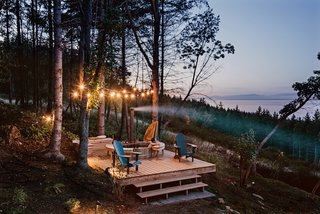 Because the interior of the home is so compact, the addition of an outdoor living room on a deck, complete with a jacuzzi, Adirondack chairs for relaxing, and some extra storage, is a great benefit.