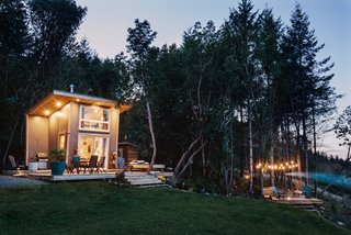 The deck near the home and the porch surrounding the house are lit up at night to allow for entertaining and outdoor living.
