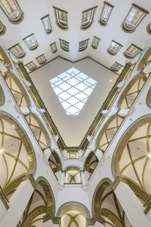 The geometry of the skylight reflects the shape of the courtyard itself and is inspired by the vaults of the arcade around it; the daylight still floods the space, allowing the green tile to contrast against the white walls.