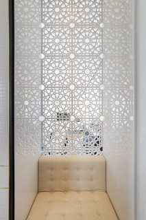 Motifs from the skylight and decorative elements of the arcade were incorporated into many of the public spaces of the hotel, like this niche with a seat and intricate geometric screen behind.